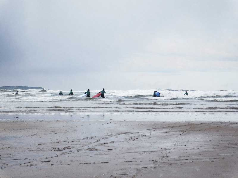 Surfers entering the water in Bundoran, Ireland